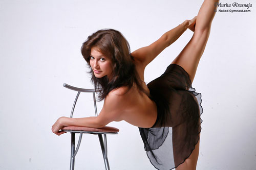 Active leg stretch by a naked flexible gymnast