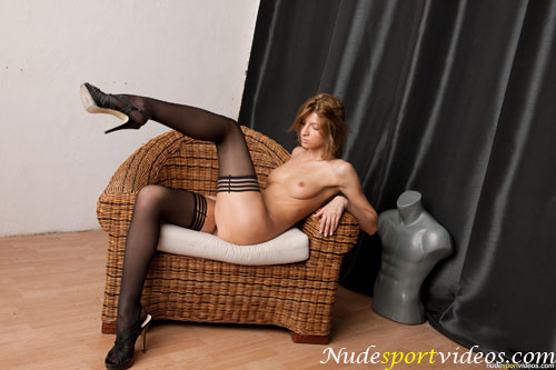 Leggy flexible girl posing in the chair in the stockings