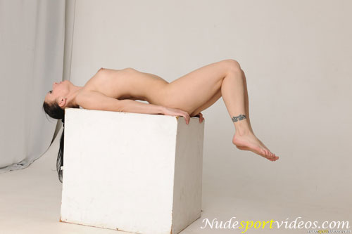 Naked gymnastics balance on an exercise cube